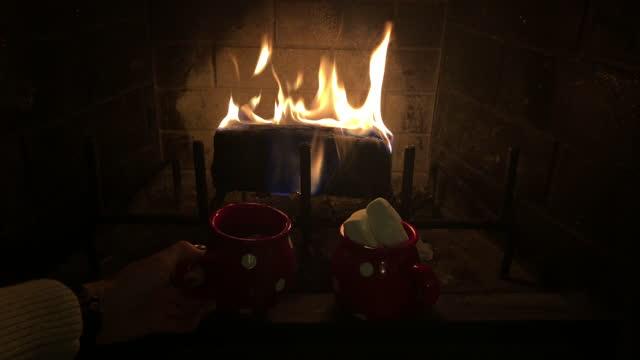 vídeos de stock, filmes e b-roll de lareira de natal queimada com duas canecas com cacau quente - chocolate quente
