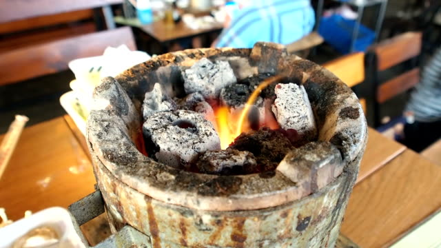 Burning fire and bright coals in stove on the table at thai bbq restaurant. video