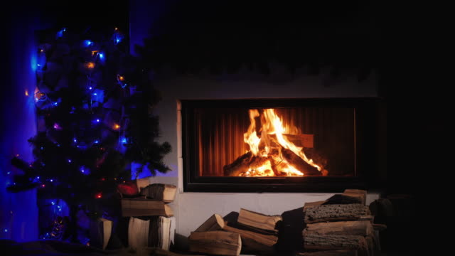 Burning fireplace decorated for Christmas, near the New Year tree video