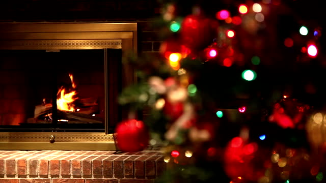 Burning Fireplace Shifting Focus to Decorated Christmas Tree Static Shot of a Fire Burning in a Brick Fireplace with an Out of Focus Decorated Christmas Tree in the Foreground. Focus Changes to the Christmas Tree. fireplace stock videos & royalty-free footage