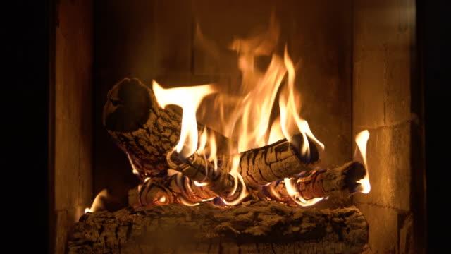 camino in fiamme con tronchi di legno e fiamma all'interno. luce calda, atmosfera romantica al coperto - camino video stock e b–roll