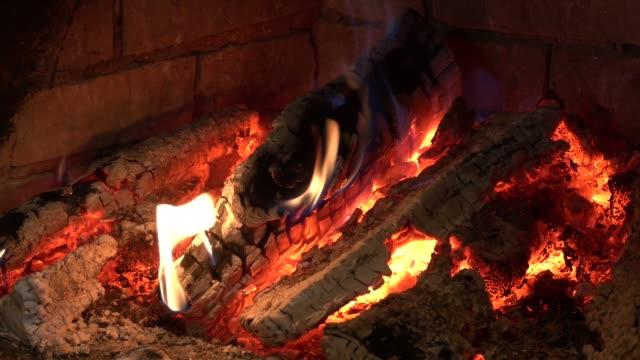 vídeos de stock e filmes b-roll de burning firewood in the fireplace close up. burning firewood in the fireplace close up. inside a blazing wood - burned oven