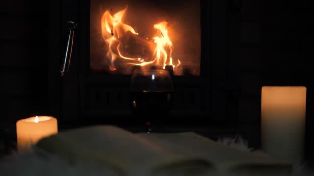 şöminede yanan yakın alev yanan mumlar ve açık bir kitap yatıyor - mum aydınlatma ürünleri stok videoları ve detay görüntü çekimi