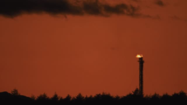 burning industrial pipe at shale gas producing mine in setting sun light - opec video stock e b–roll