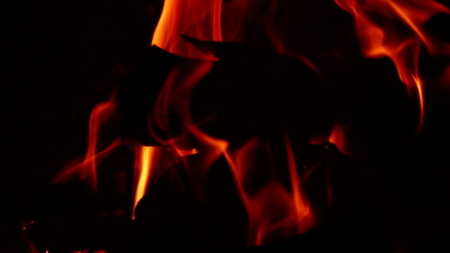 Burning logs in fire on black background in slow motion video