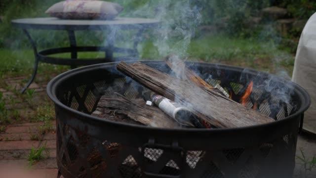 brennenden maschinenbordbücher über einem feuer als rauch wogen - mittlere schuss - brennholz stock-videos und b-roll-filmmaterial