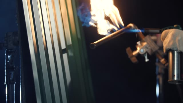 Burning of grey metal siding with butane torch. in dark. Close-up