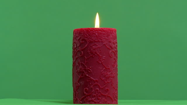 Burning red candle on a green screen