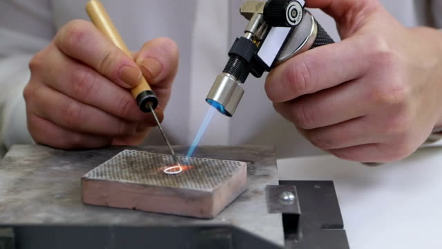 Burning silver jewelry with white gems video