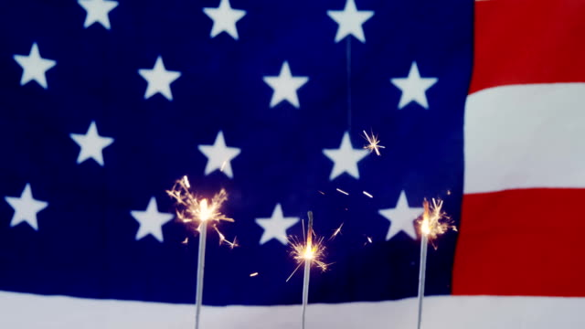 Burning sparkler on decorated cupcakes Burning sparkler on decorated cupcakes against American flag fourth of july videos stock videos & royalty-free footage