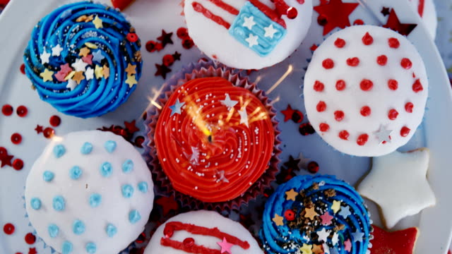 burning sparkler on decorated cupcakes - giorno dell'indipendenza video stock e b–roll