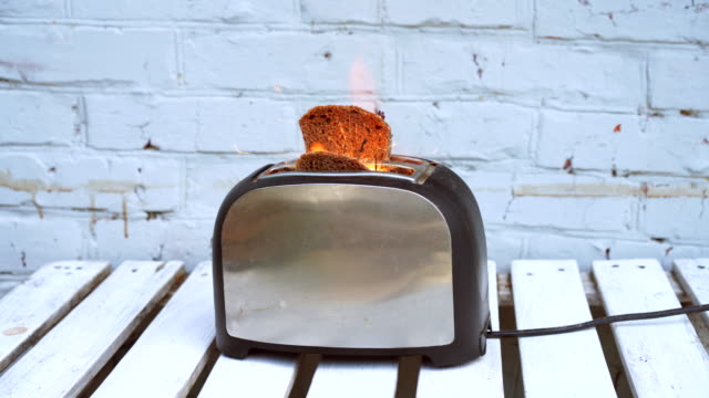 vídeos de stock e filmes b-roll de burning toaster. toaster with two slices of toast caught on fire over white background - burned cooking