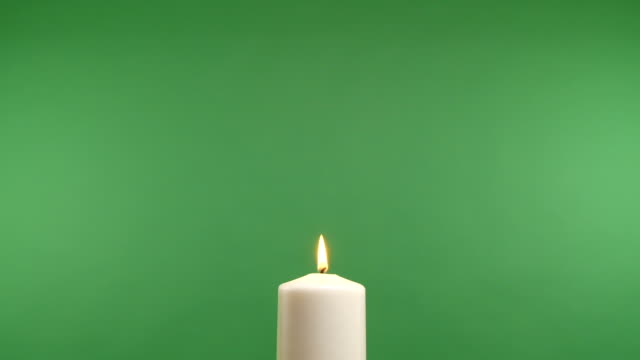 Burning white candle on a green screen