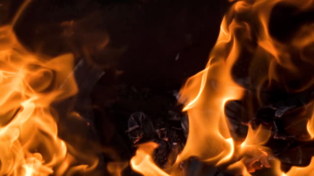 Burning wood and coal in fireplace. Closeup of hot burning wood, coals video
