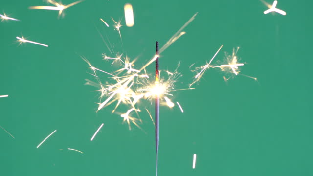 Burning yellow sparkler close up on green background cinemagraph video