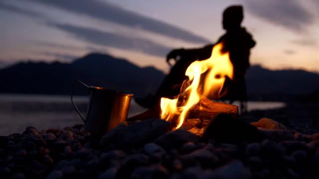 yanında demir bir kupa duran bir ateş yakar ve bulutların yüzdüzdüğü ufukta deniz ve dağların arka planına karşı bir adam dinlendirirken - şenlik ateşi stok videoları ve detay görüntü çekimi