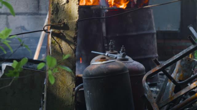 vídeos de stock e filmes b-roll de burnt lpg bottles - inflamável