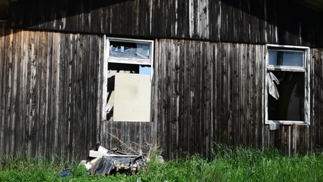 Burnt old abandoned wooden barrack house with shattered window glass in the anti emigrant protests Burnt old abandoned wooden barrack house with shattered window glass in the anti emigrant protests homeless person stock videos & royalty-free footage