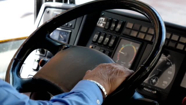 Bus driver hands on steering wheel close up video