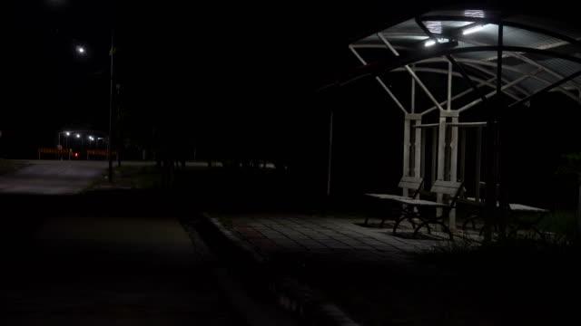 夜のバス停。ホラー映画を撮影します。 - 人の居住地点の映像素材/bロール