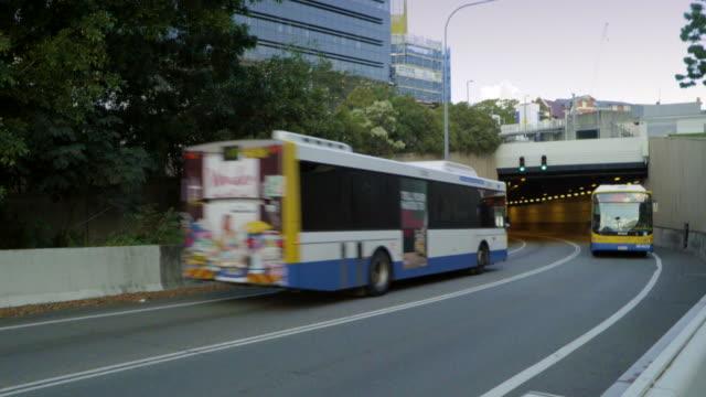 gli autobus attraversano l'ingresso del tunnel - autobus video stock e b–roll