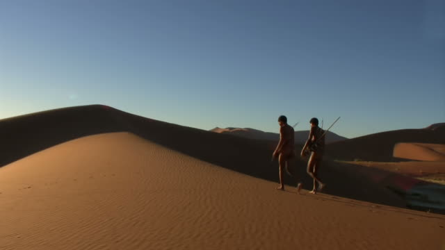 Bush people on namib dunes Steadycam-shot of very dry landscape in the Namib desert of Namibia, Africa - two bush people, father and son, walking namibia stock videos & royalty-free footage