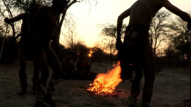 Bushmen family doing tradiitonal dance around a fire video