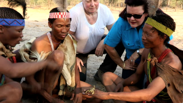 bushmen showing tourists a scorpion - ekoturystyka filmów i materiałów b-roll