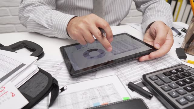 Business analysis and accounting concept - businessman working with document, spreadsheet, using calculator, tablet pc. Office desk closeup. Business analysis and accounting concept - businessman working with document, spreadsheet, using calculator, tablet pc. Office desk closeup. form filling stock videos & royalty-free footage