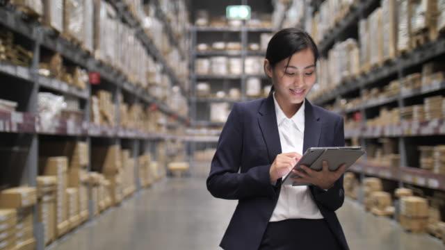 vídeos y material grabado en eventos de stock de mujeres asiáticas de negocios sosteniendo en la tableta digital en su mano en el almacén. comprobación de pedidos en stock - suministros escolares