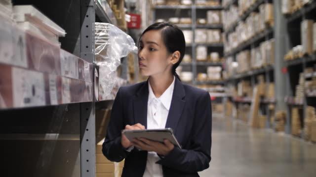 vídeos y material grabado en eventos de stock de mujeres asiáticas de negocios uso en tableta digital en el almacén. comprobación de pedidos en stock - suministros escolares