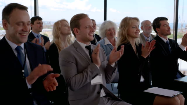 Business audience applaud at training video
