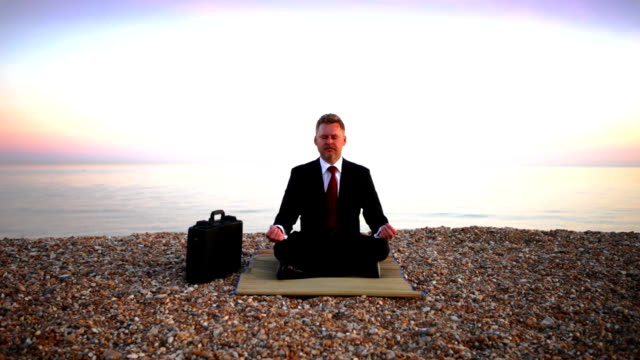 Business beach meditation A businessman in a suit and tie with briefcase meditating on a pebble beach with the sea lapping gently in the background on a calm, peaceful evening. cross legged stock videos & royalty-free footage