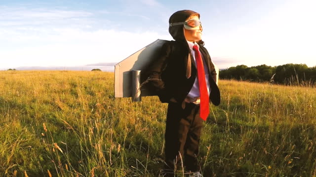 Business Boy stands confidently in English Field with jet pack A young boy uses his imagination to take his business ideas to new heights. He is standing in an English grass meadow with success on his mind. Slow motion video. bolos stock videos & royalty-free footage