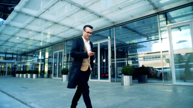 business cluster building and a man walking near operating a phone. - azionare video stock e b–roll