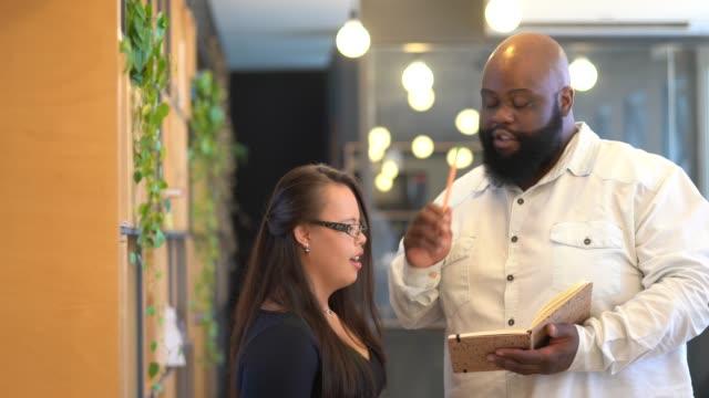 vídeos y material grabado en eventos de stock de colega de negocios (incluyendo mujeres con necesidades especiales) discutiendo ideas sobre work studio - consejero de la escuela