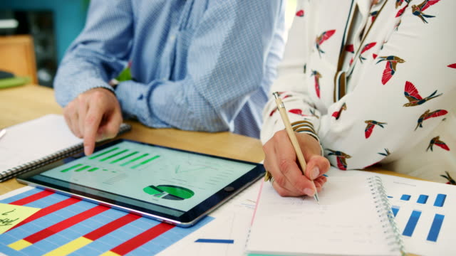business colleagues analysing financial data at their office - strategia biznesowa filmów i materiałów b-roll