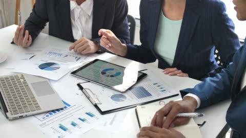 vidéos et rushes de collègues d'affaires analysant les données financières à leur bureau, stratégies d'affaires - analyser