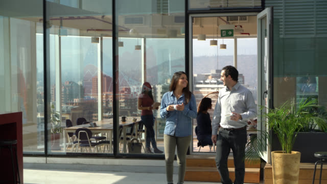 business colleagues at the office walking to the outdoor terrace of the office with a cup of coffee talking and smiling - terrazza video stock e b–roll