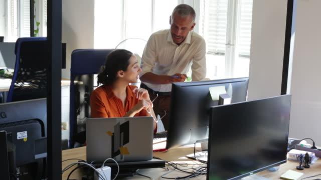 vídeos de stock e filmes b-roll de business colleagues discussing over computer - duas pessoas