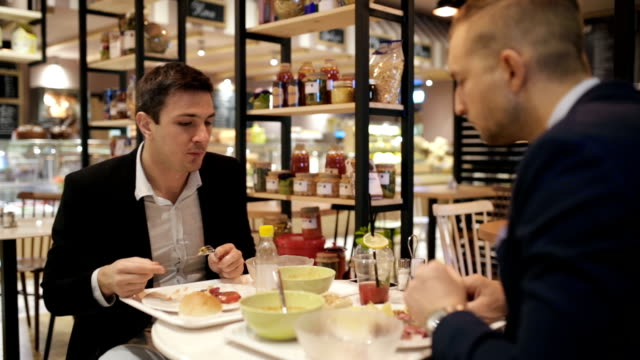 Business colleagues having lunch, handheld shot video