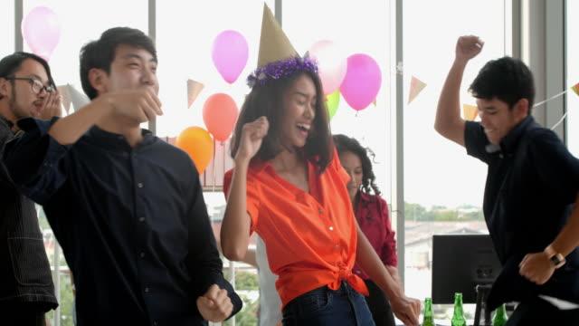 affärskollegor har fest på kontor. casual business-team som firar med champagne och party horn på kontoret - tjänstekvinna bildbanksvideor och videomaterial från bakom kulisserna