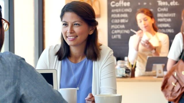 Compañeros de trabajo se reúnen en la cafetería antes del trabajo para discutir el proyecto actual - vídeo