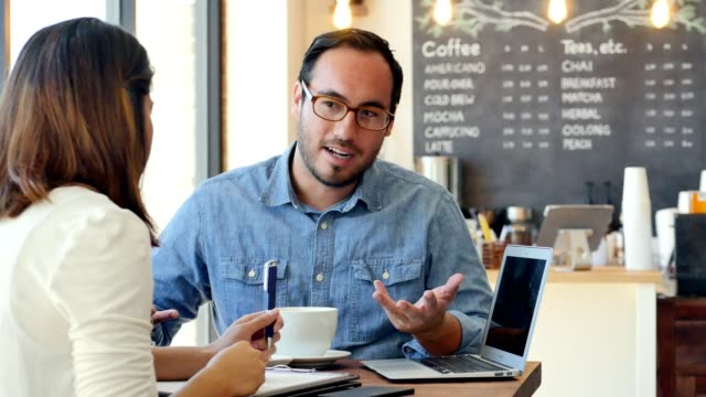 Business colleagues meet in a cafe to discuss their project before work Confident businessman discusses something with a female colleague. They are meeting before work in a coffee shop. The businessman is pointing to something on his laptop. He gestures while he talks with his colleague. owner stock videos & royalty-free footage