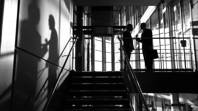 Business colleagues meet on stairwell video