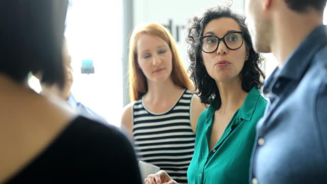 vídeos de stock e filmes b-roll de business colleagues sharing ideas in meeting - envolvimento dos funcionários