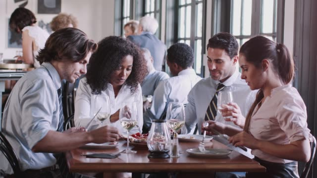 business colleagues sitting around restaurant table enjoying meal together - collega d'ufficio video stock e b–roll