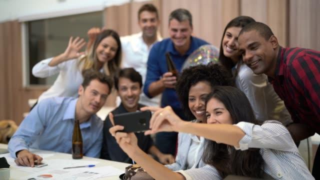colleghi di lavoro che si fanno un selfie alla festa di compleanno al lavoro - collega video stock e b–roll