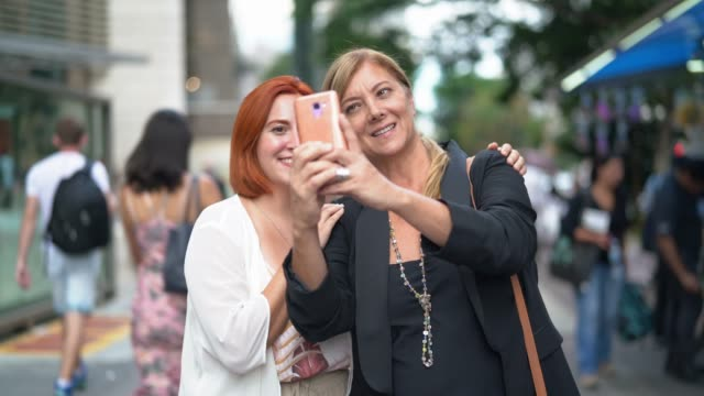 Business colleagues (mother and daughter) taking a selfie on the city