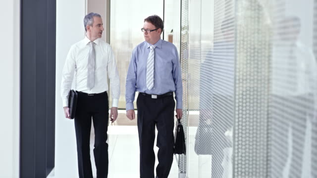 stockvideo's en b-roll-footage met slo mo business collega's praten en lopen in de hal - overhemd en stropdas